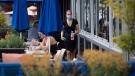A server wears a face mask as two women have drinks on the patio at an Earls restaurant, in Vancouver, on Tuesday, May 19, 2020. (THE CANADIAN PRESS / Darryl Dyck)