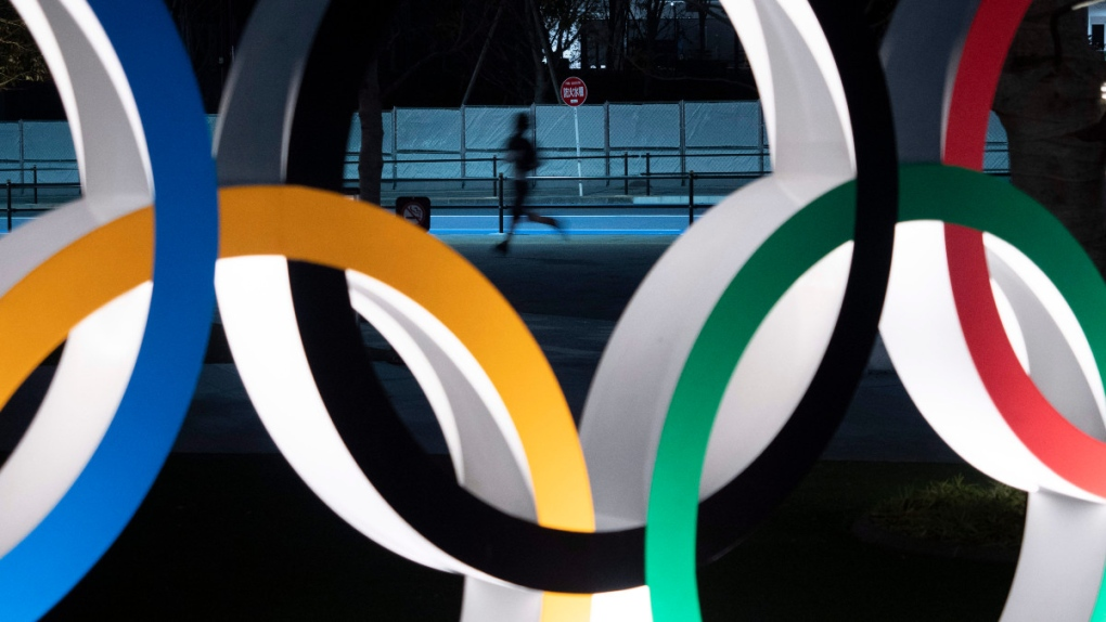 A man jogs past the Olympic rings in Tokyo