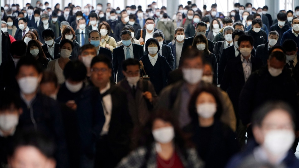A station passageway is crowded with commuters wearing face masks in Tokyo, on April 27, 2020. (Eugene Hoshiko / AP)
