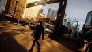 A pedestrian wearing a mask walks down the empty streets of downtown Edmonton as people stay in to protect against getting the COVID-19 virus, in Edmonton on Sunday March 22, 2020. THE CANADIAN PRESS/Jason Franson
