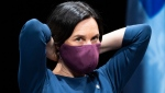 Montreal Mayor Valerie Plante slips on her protective mask during a news conference in Montreal. THE CANADIAN PRESS/Paul Chiasson