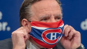 Quebec Premier Francois Legault removes a Montreal Canadiens face mask as he starts the daily COVID-19 press briefing Thursday May 21, 2020 in Montreal.THE CANADIAN PRESS/Ryan Remiorz