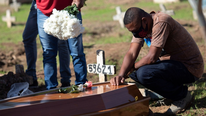 A man cries over the casket of 22-year-old COVID-19 victim Amanda da Silva at the Caju cemetery in Rio de Janeiro, Brazil, Wednesday, May 20, 2020. (AP / Silvia Izquierdo)