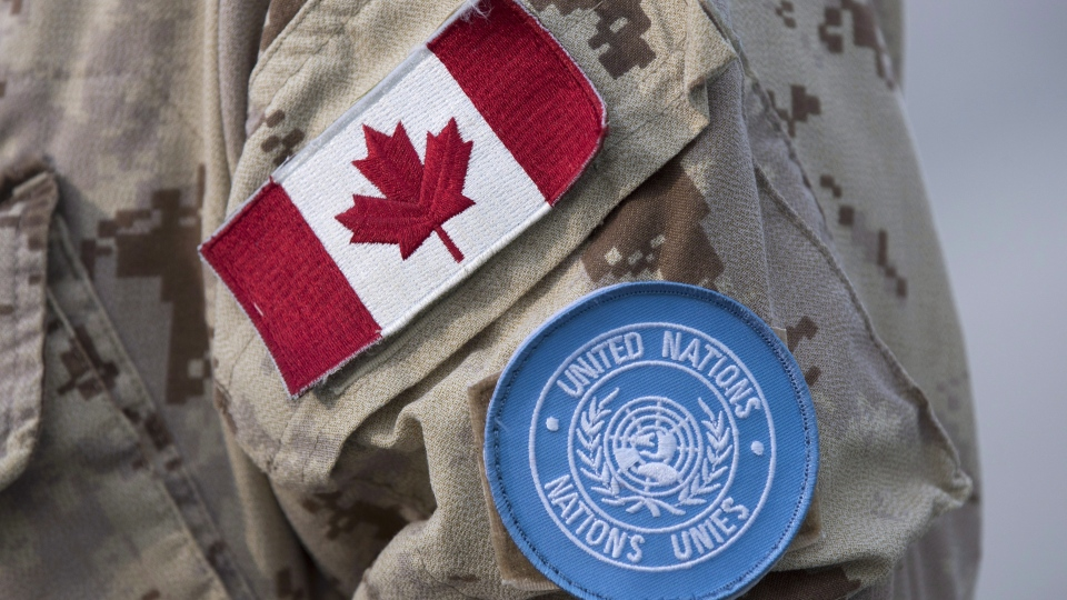 Canadian flag and the UN flag is shown on the sleeve of a Canadian soldier's uniform before boarding a plane at CFB Trenton in Trenton, Ont., on July 5, 2018. (THE CANADIAN PRESS/Lars Hagberg)