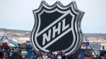 In this Saturday, Feb. 15, 2020, file photo, fans pose below the NHL league logo at a display outside Falcon Stadium before an NHL Stadium Series outdoor hockey game between the Los Angeles Kings and Colorado Avalanche, at Air Force Academy, Colo. (AP Photo/David Zalubowski, File)