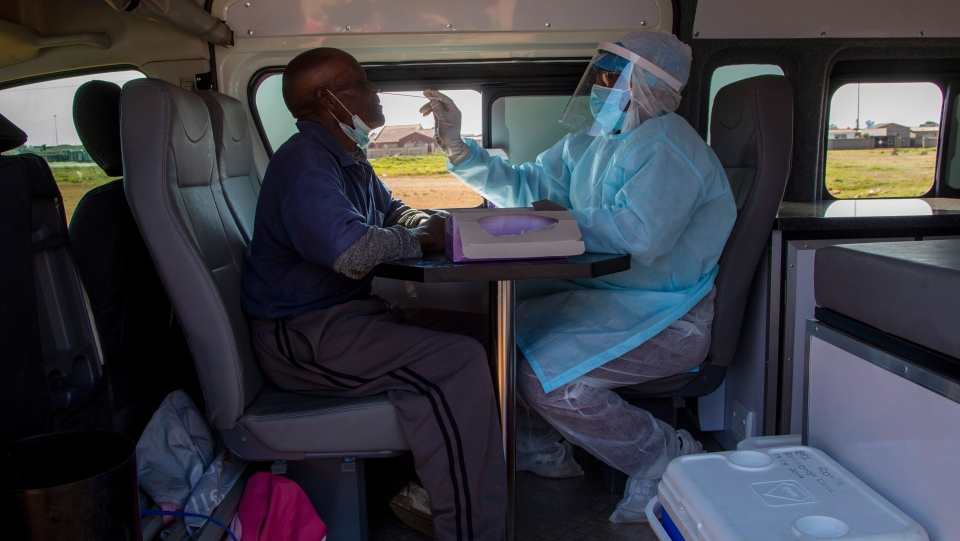 A heath worker collects a sample for coronavirus testing from a man inside a mobile clinic during the screening and testing campaign aimed to combat the spread of COVID-19 at Sphamandla informal settlement in Katlehong, south of Johannesburg, South Africa, Friday, May 22, 2020. (AP Photo/Themba Hadebe)