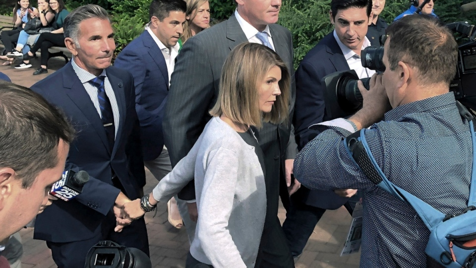 Lori Loughlin departs federal court with her husband, Mossimo Giannulli, left, in Boston, on Aug. 27, 2019. (Philip Marcelo / AP)