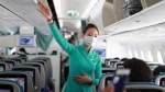 A flight attendant gives instructions to passengers on a plane in Ho Chi Minh City, Vietnam on Monday, March 16, 2020. (AP Photo/Hau Dinh)