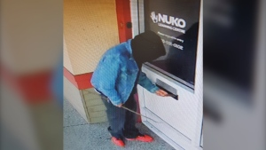 "Surveillance video of the incident - shot between 3 a.m. and 5 a.m. on May 15 at NUKO's office at 60 Needham St. - shows a man ""using a long stick to fish out"" a pair of Nike high-tops from a slot in the building's door, police said. (Nanaimo RCMP)"