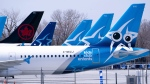 Air Transat and an Air Canada aircrafts are seen on the tarmac at Montreal-Trudeau International Airport in Montreal, on Wednesday, April 8, 2020. THE CANADIAN PRESS/Paul Chiasson