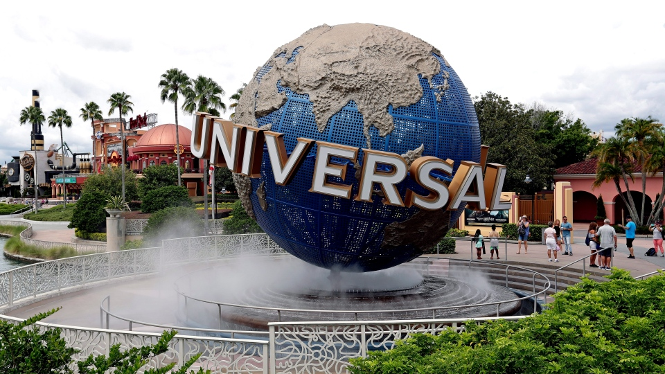In this Aug. 5, 2019 file photo, guests cool off under a water mist by the globe at Universal Studios City Walk at Universal Studios Florida in Orlando, Fla.