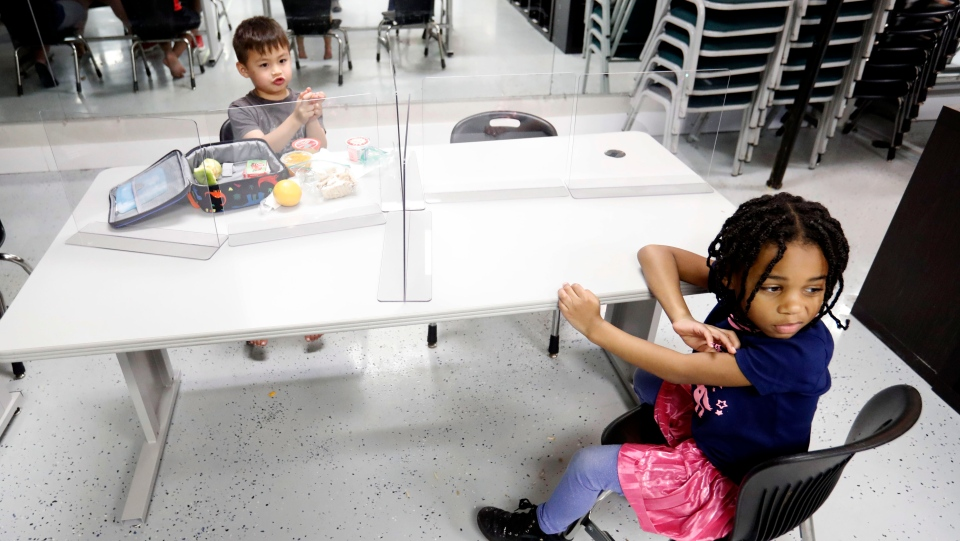 Plastic barriers are placed between Bruce McCall, 5, left, and Capri Bishop, 6, as they sit at a table during martial arts daycare summer camp at Legendary Blackbelt Academy in Richardson, Texas, Tuesday, May 19, 2020. (AP Photo/LM Otero)
