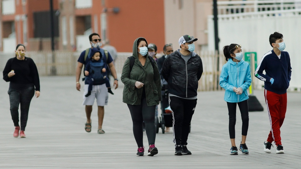 Pedestrians wear protective masks during the coronavirus pandemic while walking on the boardwalk Friday, May 22, 2020, in Long Beach, N.Y. (AP Photo/Frank Franklin II)