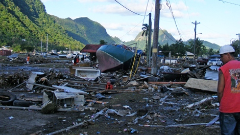 A resident walks past debris in a playground and a tennis park left by the tsuami that struck Pago Pago, American Samoa, Tuesday Sept. 29, 2009. (AP / Fili Sagapolutele)