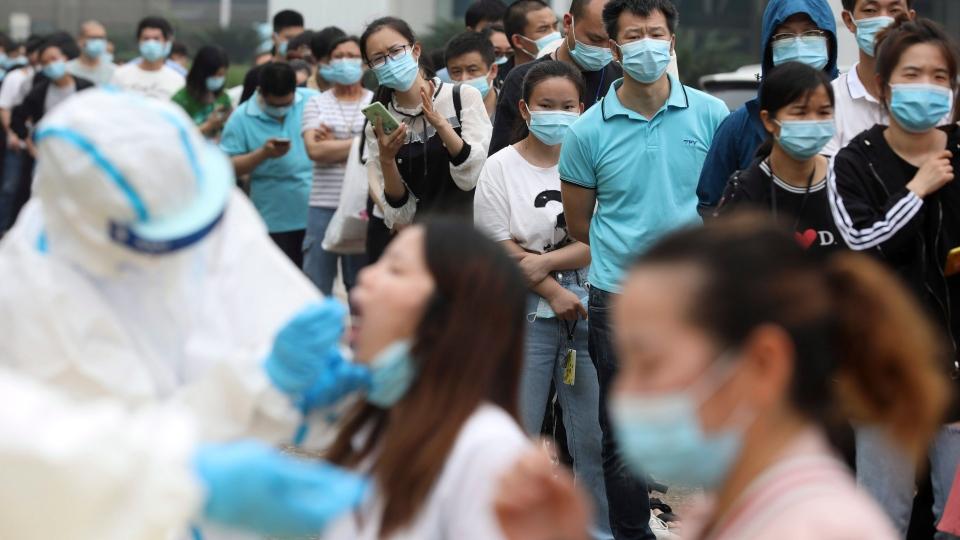 Workers line up for medical workers to take swabs for the coronavirus test at a large factory in Wuhan in central China's Hubei province Friday, May 15, 2020. (Chinatopix Via AP)