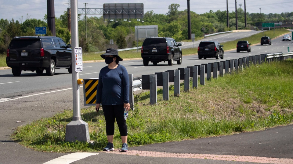 A woman wears a mask as she waits for the motorcade for U.S. President Donald Trump to go past, Saturday, May 23, 2020, in Sterling, Va. Trump is en route to Trump National Golf Club. (AP Photo/Alex Brandon)