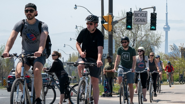 Cyclists negotiate a road crossing on a bike path in Toronto on Saturday, May 23, 2020. Warm weather and a reduction in COVID-19 restrictions has many looking to the outdoors for relief. THE CANADIAN PRESS/Frank Gunn