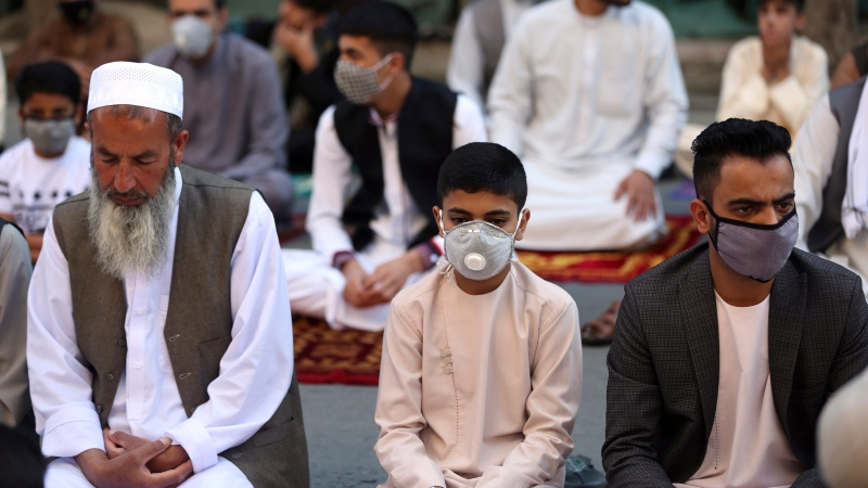 Men wait to attend Eid al-Fitr prayers outside a mosque in Kabul, Afghanistan, Sunday, May 24, 2020. (AP Photo/Rahmat Gul)