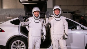 In this Friday, Jan. 17, 2020 photo made available by NASA, astronauts Doug Hurley, left, and Robert Behnken pose in front of a Tesla Model X car during a SpaceX launch dress rehearsal at Kennedy Space Center in Cape Canaveral, Fla. (Kim Shiflett/NASA via AP)