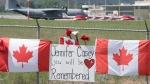 The Canadian Forces Snowbirds jets are seen in the background as Canadian flags are attached to the fence at the Kamloops airport in Kamloops, B.C., Monday, May 18, 2020. Capt. Jenn Casey died Sunday after the Snowbirds jet she was in crashed shortly after takeoff. The pilot of the aircraft is in hospital with serious injuries. THE CANADIAN PRESS/Jonathan Hayward