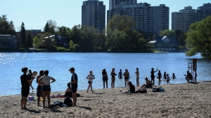 People practice physical distancing as they enjoy the warm weather at Mooney's Bay Beach in Ottawa, on Saturday, May 23, 2020, in the midst of the COVID-19 pandemic. THE CANADIAN PRESS/Justin Tang