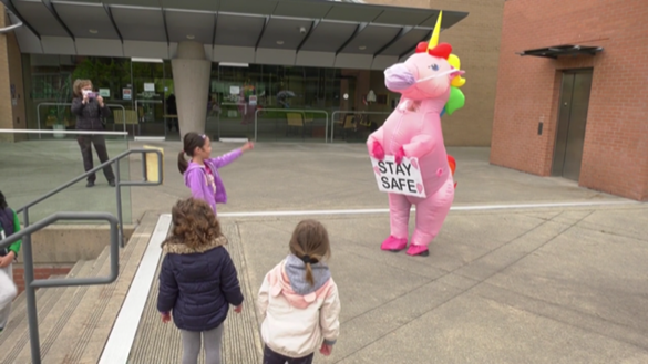 Workers at Coquitlam city hall were treated to an unusual sight Friday afternoon: a bright pink unicorn with rainbow mane, waddling up the front steps to wave to staff through the glass. (CTV)