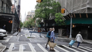 Pedestrians wearing protective masks cross Irving Place during the coronavirus pandemic Saturday, May 23, 2020, in New York. (AP Photo/Frank Franklin II)