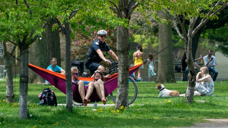 A bicycle police officer patrols Trinity Bellwoods Park in Toronto on Sunday, May 24, 2020. Warm weather and a reduction in COVID-19 restrictions has many looking to the outdoors for relief. (THE CANADIAN PRESS/Frank Gunn)