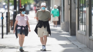 A man and woman wear face maks as they walk along Sainte-Catherine street in Montreal, Sunday May 24, 2020, as the COVID-19 pandemic continues in Canada and around the world. Stores with a street entrance are allowed to reopen in Montreal on May 25th. THE CANADIAN PRESS/Graham Hughes
