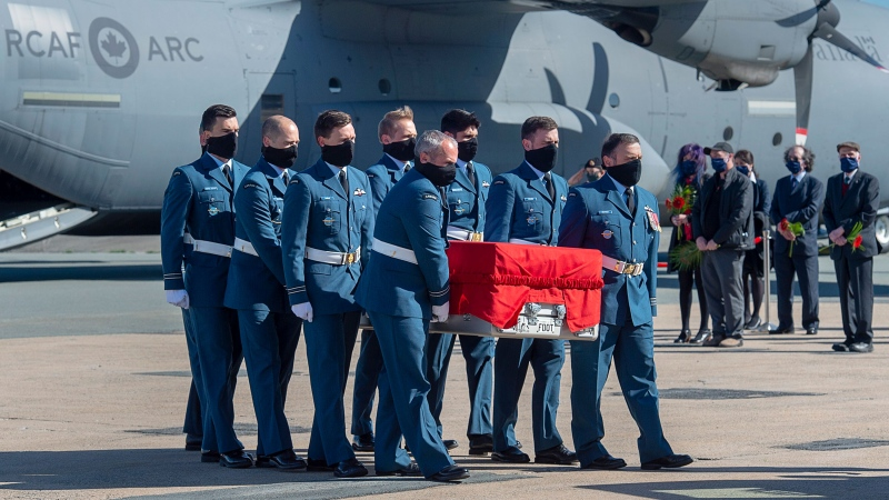 Pall bearers carry the casket of RCAF Capt. Jennifer Casey past her family members during a homecoming ceremony at Halifax Stanfield International Airport in Enfield, N.S. on Sunday, May 24, 2020. Casey, a military public affairs officer and a Halifax native, was killed in the crash of a Snowbirds Tutor jet in a residential area of Kamloops, B.C.. THE CANADIAN PRESS/Andrew Vaughan