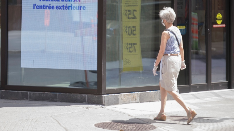 A woman walks by a store on Sainte-Catherine street in Montreal, Sunday May 24, 2020, as the COVID-19 pandemic continues in Canada and around the world. Stores with a street entrance are allowed to reopen in Montreal on May 25th. THE CANADIAN PRESS/Graham Hughes
