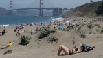 Sara Stewart, foreground, reads a book while away from crowds visiting Baker Beach during the coronavirus outbreak in San Francisco, Sunday, May 24, 2020. (AP Photo/Jeff Chiu)