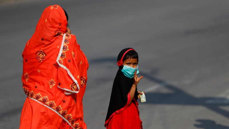 A Nepalese Muslim girl walks with her mother after shopping during Eid al-Fitr in Kathmandu, Nepal, Monday, May 25, 2020. (AP Photo/Niranjan Shrestha)