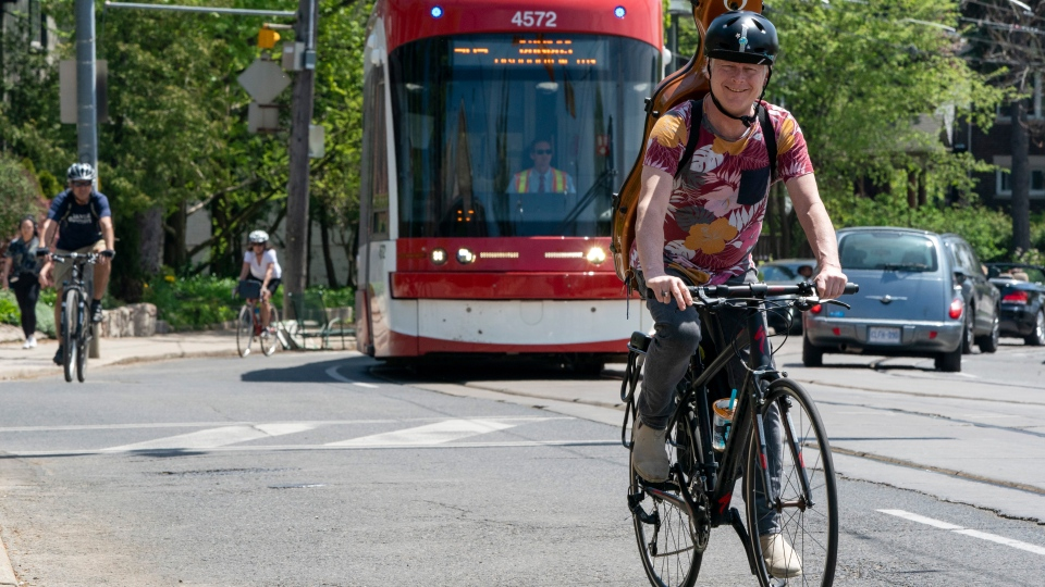 Cyclists ride up a hill with a TTC streetcar in Toronto on Saturday, May 23, 2020. COVID-19 is causing commuters to examine various modes of transportation that allow for physical distancing. THE CANADIAN PRESS/Frank Gunn