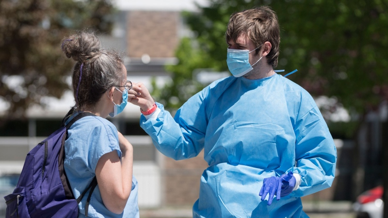 Health-care workers talk next to a mobile COVID-19 testing clinic in the Montreal neighbourhood of Verdun, Saturday, May 23, 2020, as the COVID-19 pandemic continues in Canada and around the world. THE CANADIAN PRESS/Graham Hughes