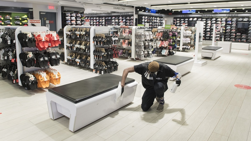 Liam Slater Oda, an employee with Sports Experts disenfects a bench at the store on Sainte-Catherine street in Montreal, Sunday May 24, 2020. THE CANADIAN PRESS/Graham Hughes