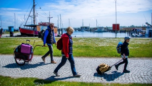 Tourists with backpacks and suitcases arrives at the port of Kloster on the Baltic island Hiddensee in Vitte, Germany, Monday May 25, 2020. In German state Mecklenburg-Western Pomerania, after the travel ban due to the coronavirus protection measures, holidaymakers from other federal states are now allowed to travel to the island. ( Jens Buettner/dpa via AP)