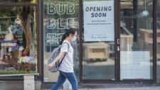 A woman wears a face mask as she walks along Sainte-Catherine street in Montreal, Sunday May 24, 2020, as the COVID-19 pandemic continues in Canada and around the world. THE CANADIAN PRESS/Graham Hughes