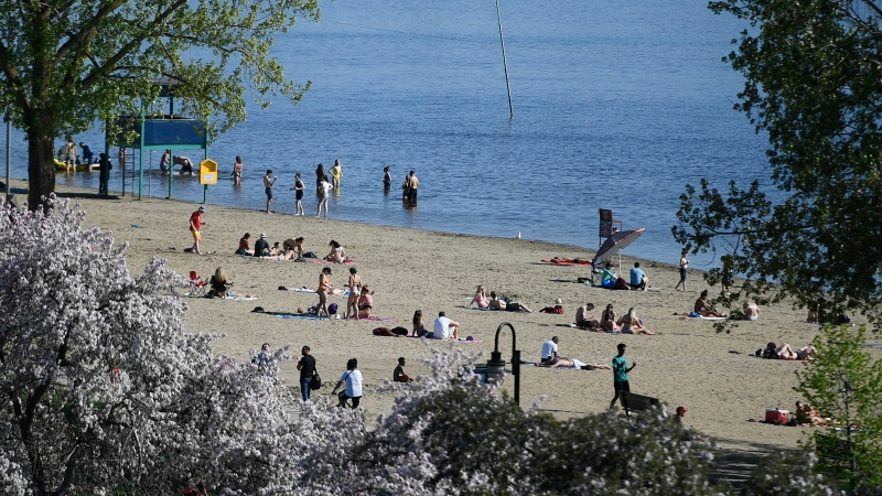 People practice physical distancing as they enjoy the warm weather at Mooney's Bay Beach in Ottawa, on Saturday, May 23, 2020, in the midst of the COVID-19 pandemic. (Justin Tang/THE CANADIAN PRESS)