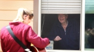 "In this April 17, 2020, photo, Lowell Havener, right, a resident of Rising Mountains Assisted Living, smiles and sings along with music therapist Kirsten Wells in Bigfork, Mont. She played songs like ""Take Me Out to the Ball Gpame,"" ""When It's Springtime in the Rockies"" and ""King of the Road."" (Mackenzie Reiss/The Daily Inter Lake via AP)"