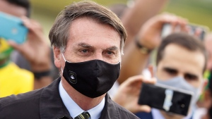 Brazil's President Jair Bolsonaro, wearing a face mask amid the new coronavirus pandemic, stands amid supporters taking pictures with cell phones as he leaves his official residence of Alvorada palace in Brasilia, Brazil, Monday, May 25, 2020. (AP Photo/Eraldo Peres)