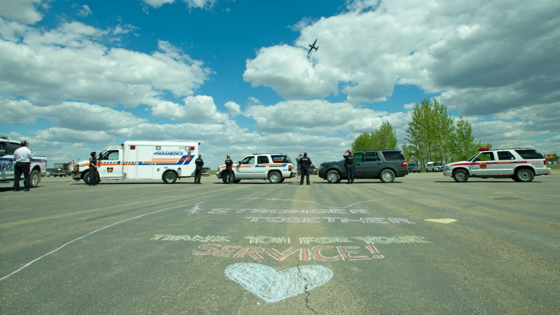 Police, paramedics, fire crews and civilians gather at the exhibition grounds in Moose Jaw to welcome the Canadian Forces Snowbirds, flying together in C-130 Hercules, home on Monday, May 25, 2020. The Snowbirds were grounded after Capt. Jennifer Casey was killed in a crash in Kamloops on May 17. THE CANADIAN PRESS/Mark Taylor.