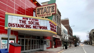 In this March 18, 2020, photo, a tongue-in-cheek message is displayed on the marquee of the State Theatre in Traverse City, Mich. The historic theater hosts the Traverse City Film Festival, led by documentary filmmaker Michael Moore, which is among many summer festivals and events in the tourist-friendly community that have been canceled because of the coronavirus. With summer vacation season looming, this town on a Lake Michigan bay normally would be expecting a crush of visitors. But some local residents have mixed feelings about crowds descending on the area, which might cause the number of virus cases to rise. (AP Photo/John Flesher)