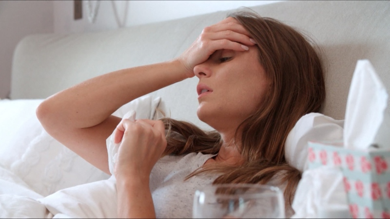 A stock photograph shows a woman sick in bed.