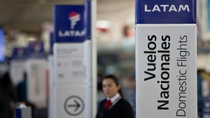 In this July 25, 2016, file photo, an agent of LATAM airlines stands by the counters at the airport in Santiago, Chile. (AP Photo/Esteban Felix, File)