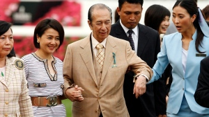 In this April 29, 2007, file photo, Macao tycoon and owner of Hong Kong horse Viva Pataca Stanley Ho, center, gets a little help from his wife Angela Leung, second left, and an attendant during awarding ceremony at the Sha Tin racecourse in Hong Kong. (AP Photo/Vincent Yu, File)