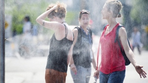 People use misters to cool down during a heatwave in Montreal. (File photo/THE CANADIAN PRESS/Graham Hughes)
