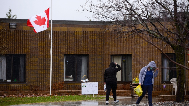 People come and go as a flag flies at half staff at an Almonte Country Haven long-term care home during the COVID-19 pandemic in Almonte, Ontario on Monday, April 13, 2020. The 82-bed home reported 14 deaths due to COVID-19 and 36 residents have tested positive for the virus. THE CANADIAN PRESS/Sean Kilpatrick