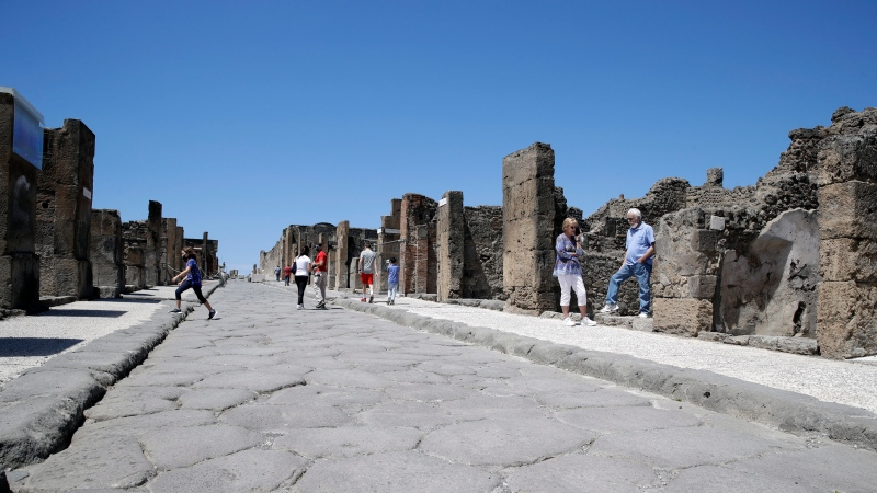 Colleen and Marvin Hewson, right, from the United States, visit the archeological site of Pompeii, near Naples, southern Italy, Tuesday, May 26, 2020. (AP Photo/Alessandra Tarantino)