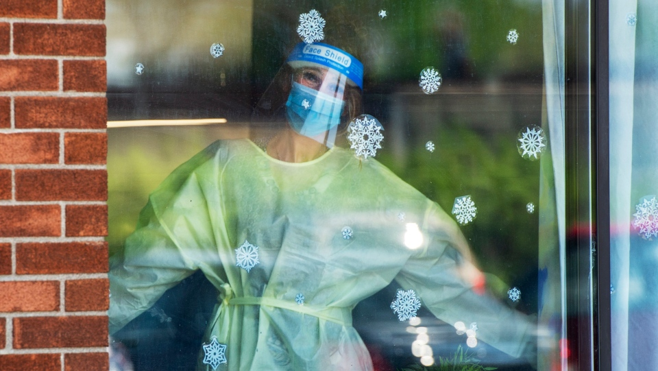 A healthcare worker is seen through the window at the Vigi Mount Royal CHSLD seniors residence Tuesday May 26, 2020 in Montreal. THE CANADIAN PRESS/Ryan Remiorz